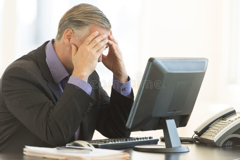 Affärsmannen With Head In räcker sammanträde på skrivbordet arkivbilder