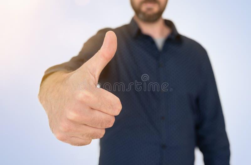 Affärsmannen i blåa skjortavisningtummar gör en gest upp royaltyfria foton