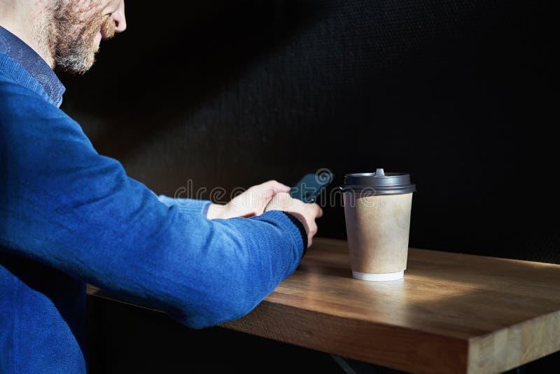 Affärsmannen i blått tröjadrinkkaffe i ett soligt kafé, närbild rymmer ett disponibelt pappers- exponeringsglas, genom att använd royaltyfri foto