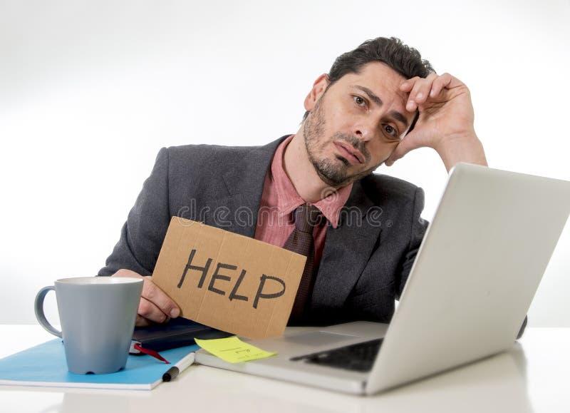 Affärsmannen i dräkt- och bandsammanträde på kontorsskrivbordet som arbetar på datorbärbara datorn som frågar för hållande papp f arkivbilder
