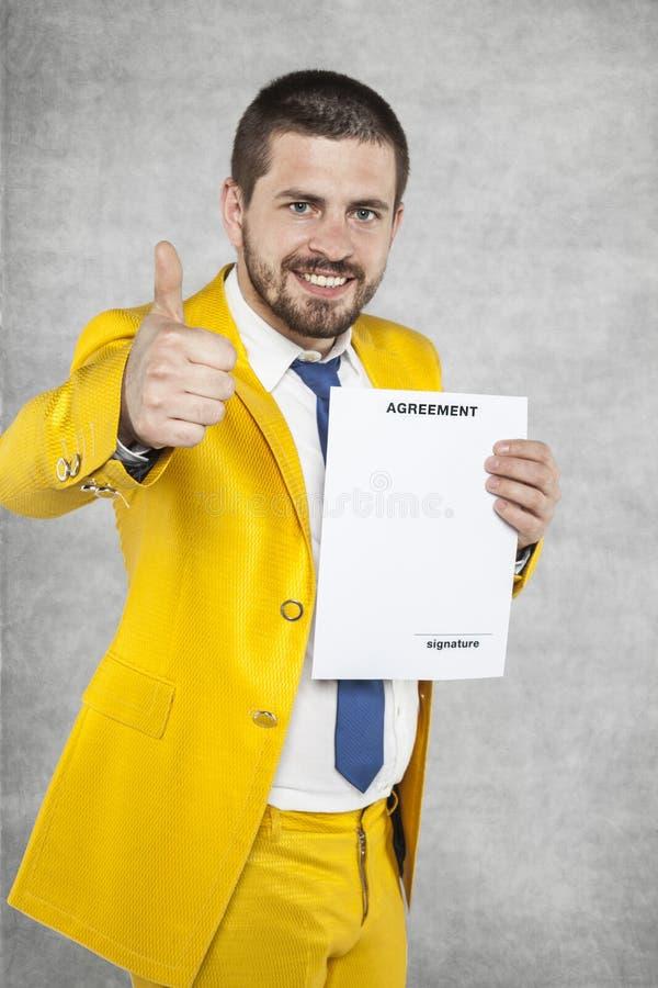 Affärsmannen i en guld- dräktvisning tummar upp, den nya överenskommelsen arkivfoto