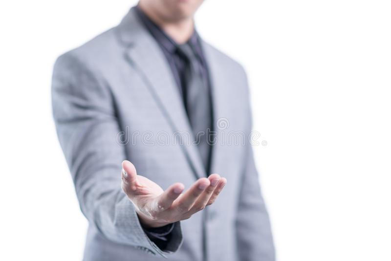 Affärsmannen i grå färgdräkt visar att något i hans tomt gömma i handflatan royaltyfri fotografi