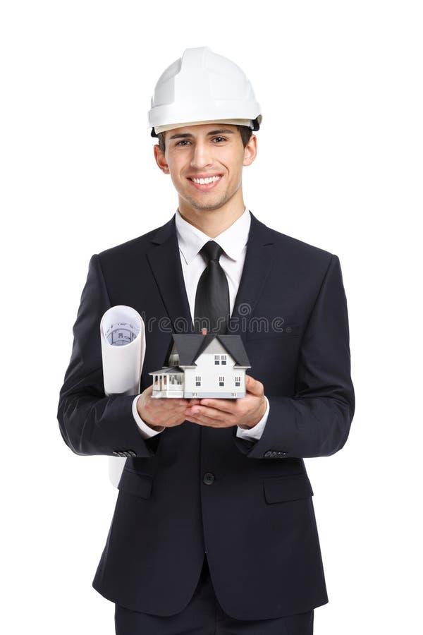 Affärsmannen i hjälmhänder modellerar huset och orienteringen arkivfoton