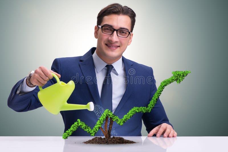 Affärsmannen i investeringbegrepp som bevattnar den finansiella linjen diagram royaltyfri bild