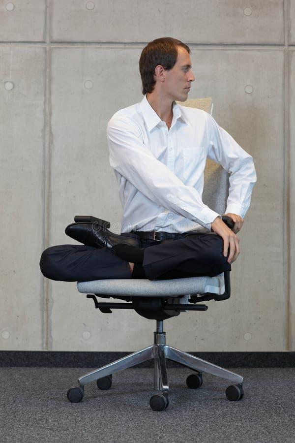 Affärsmannen i lotusblomma poserar på praktiserande yoga för kontorsstol royaltyfri bild