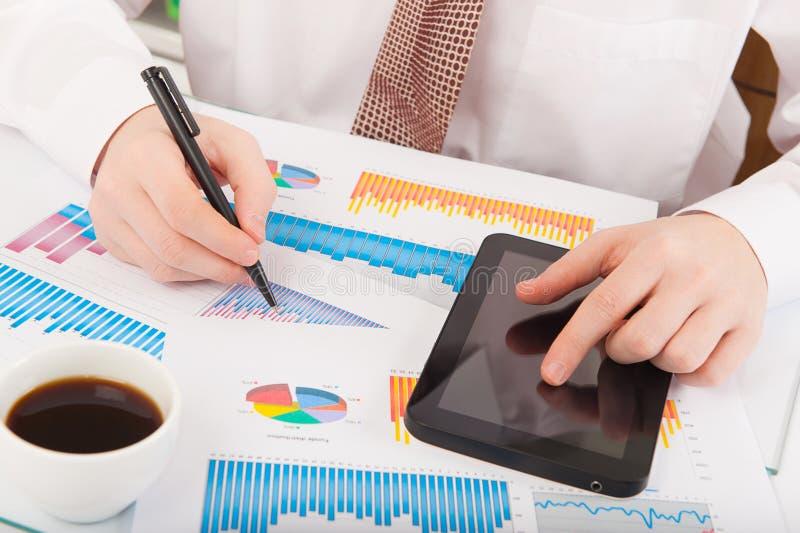 Affärsmannen som analyserar grafer och, kartlägger royaltyfri bild