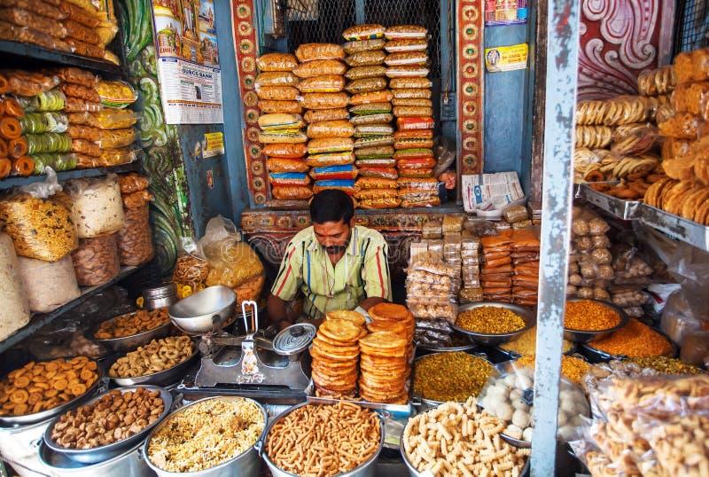 Affärsmannen inom sötsaker lagrar att sälja smakliga kex och mellanmål arkivfoton