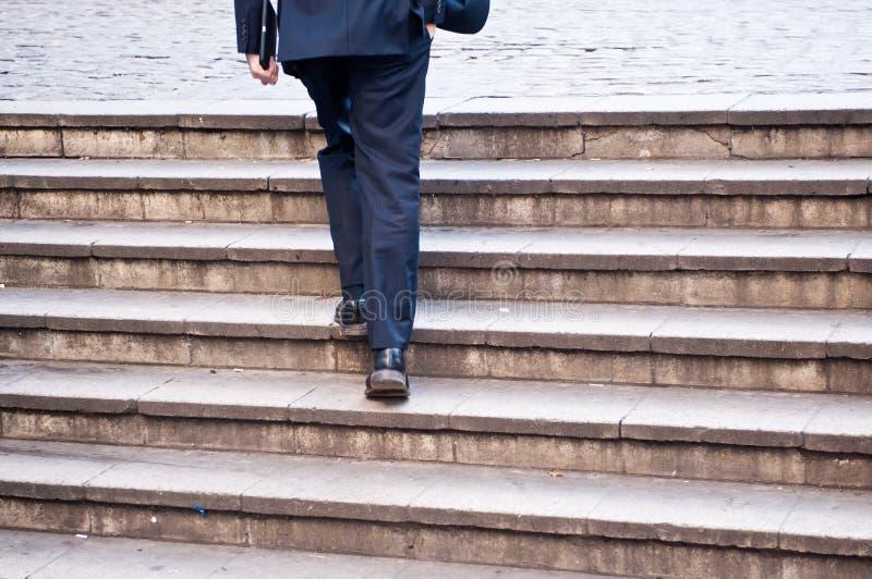 Affärsmannen klättrar ett flyg av trappa royaltyfri foto