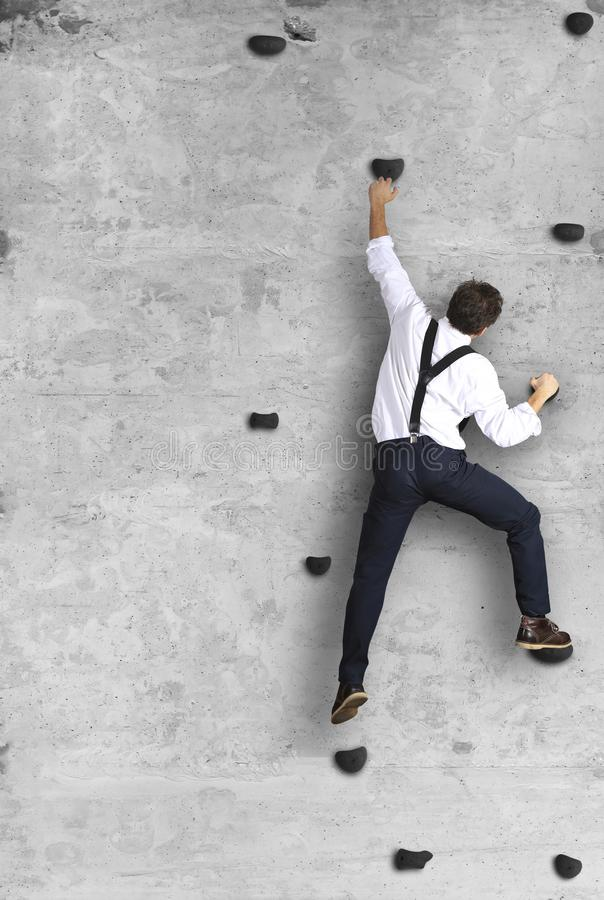 Affärsmannen klättrar väggen som en klättrare arkivbild