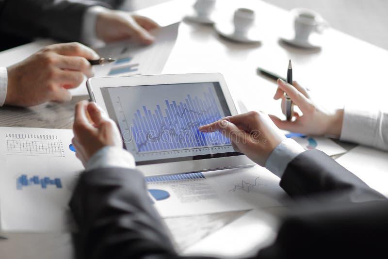 Affärsmannen kontrollerar finansiella data genom att använda en digital minnestavla Folk och teknologi arkivbilder