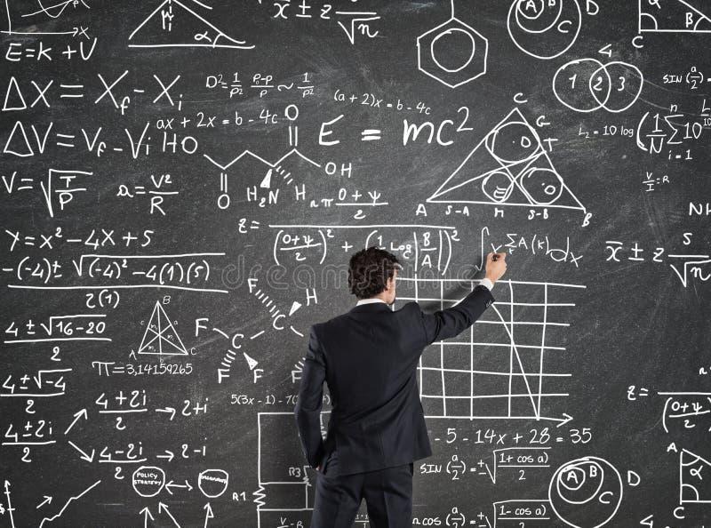 Affärsmannen löser problem med matematikberäkningar royaltyfri foto