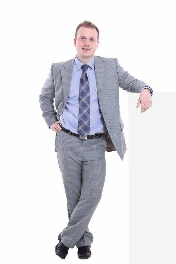 Affärsmannen lutar på en faktisk vägg royaltyfri bild