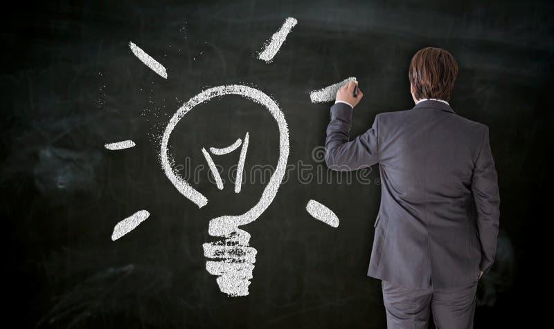 Affärsmannen målar lightbulben på svart tavlabegrepp royaltyfri bild