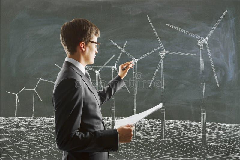Affärsmannen målar vindgeneratorer på svart tavla och bär arkivbilder