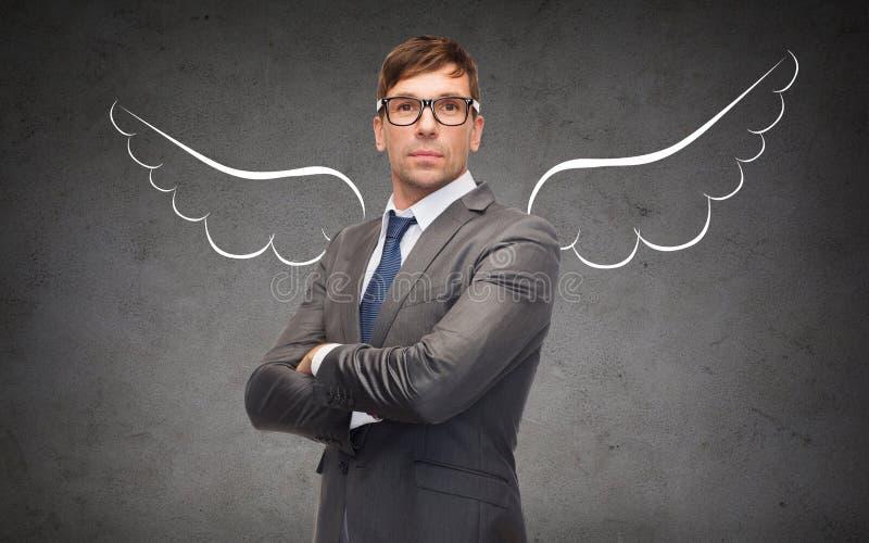 Affärsmannen med ängel påskyndar över grå färger royaltyfri bild