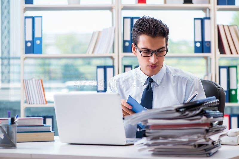 Affärsmannen med överdriven arbetsskrivbordsarbete som i regeringsställning arbetar royaltyfria foton