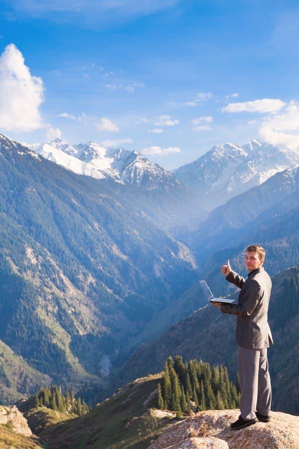 Affärsmannen med bärbara datorn av berget är upptill behar arkivbilder