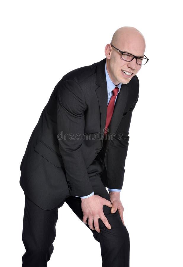 Affärsmannen med benet smärtar eller kramper royaltyfri foto