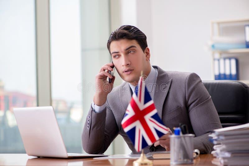 Affärsmannen med den brittiska flaggan i kontoret arkivbild