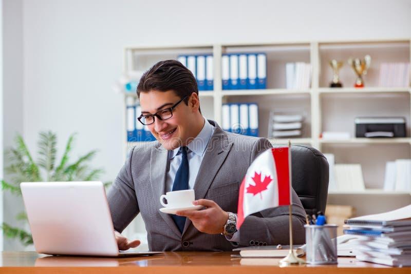 Affärsmannen med den kanadensiska flaggan i regeringsställning royaltyfri foto
