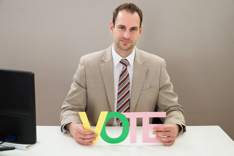 Affärsmannen med det mångfärgade ordet röstar royaltyfria foton