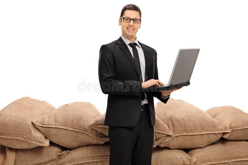 Affärsmannen med en bärbar dator som är främst av en hög av säckväv, plundrar arkivfoto