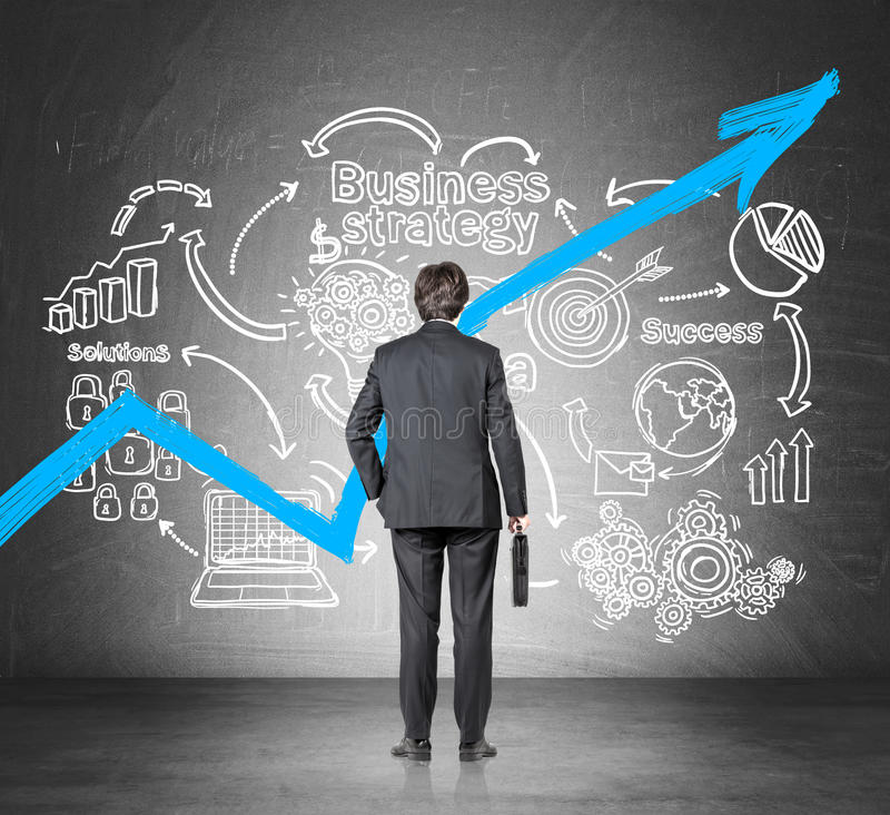 Affärsmannen med en resväska som ser en växande blå graf och en affärsstrategi, skissar arkivfoto