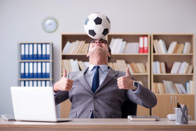 Affärsmannen med fotbollbollen i regeringsställning royaltyfri foto