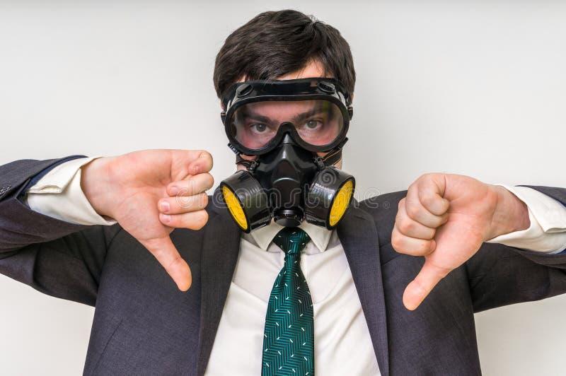 Affärsmannen med gasmasken visar negativ gest royaltyfri fotografi