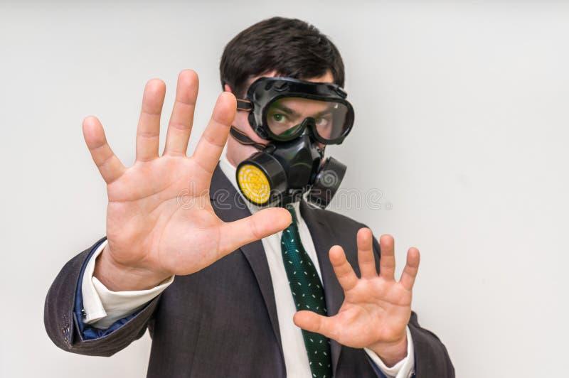 Affärsmannen med gasmasken visar stoppgest royaltyfria bilder