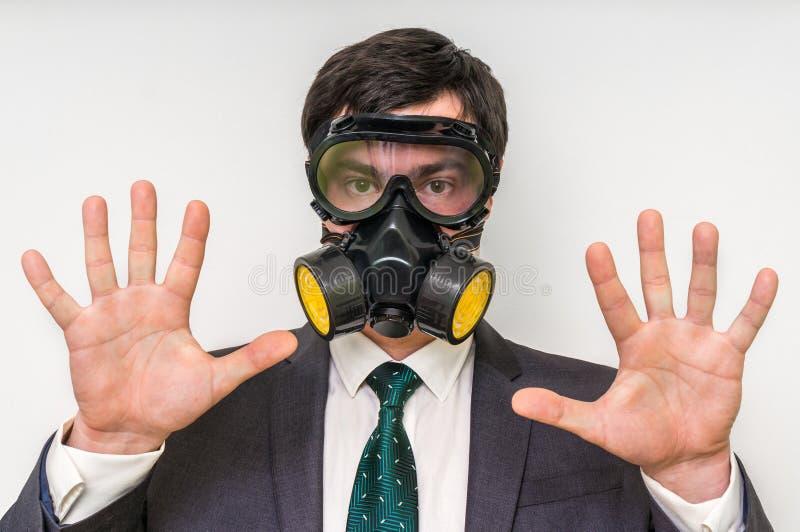 Affärsmannen med gasmasken visar stoppgest arkivfoton