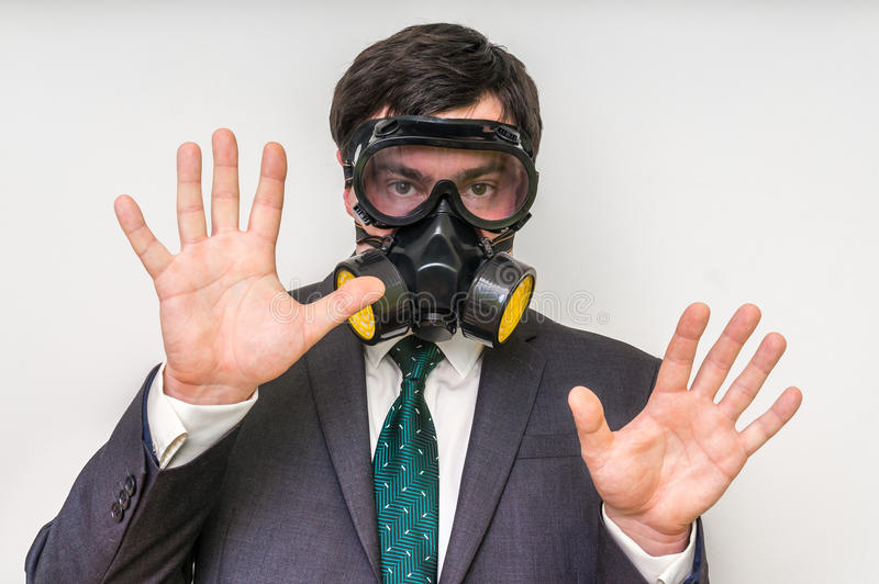Affärsmannen med gasmasken visar stoppgest royaltyfri fotografi