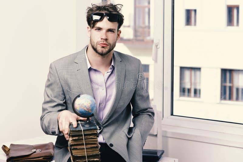 Affärsmannen med högen av böcker och jordklotet modellerar på fönsterbakgrund Betydelse av kunskapsbegreppet Kallt bära för grabb royaltyfri fotografi