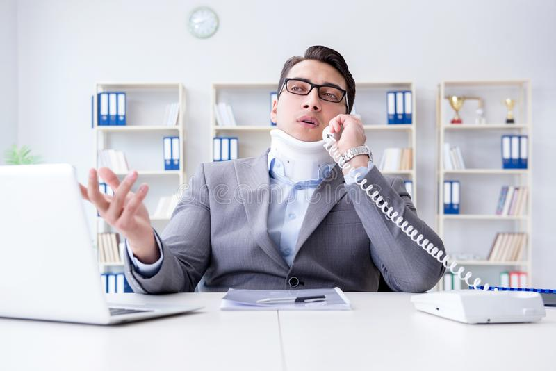 Affärsmannen med halsskadan som arbetar i kontoret royaltyfri fotografi