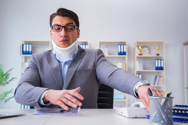 Affärsmannen med halsskadan som arbetar i kontoret royaltyfria bilder