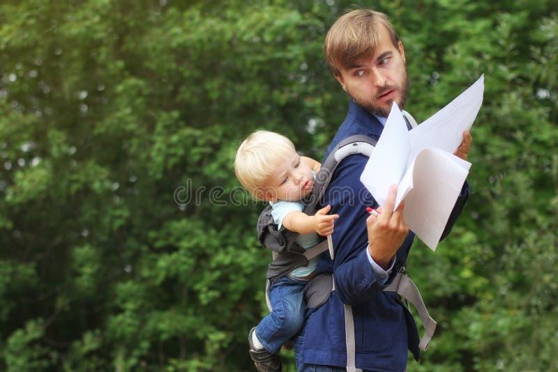Affärsmannen med hans son i en rem på baksida, visar honom avtal D arkivfoton