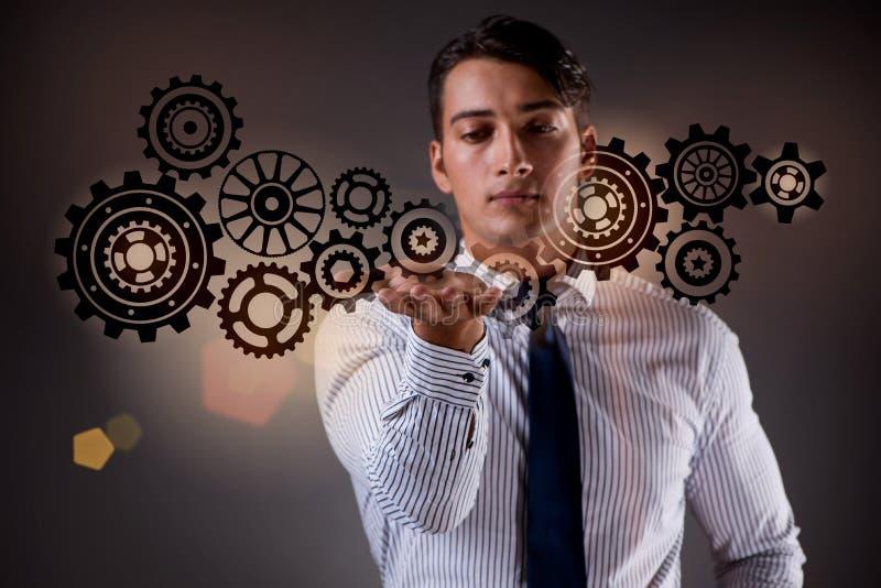 Affärsmannen med kugghjulkugghjulet i teamworkbegrepp royaltyfria bilder
