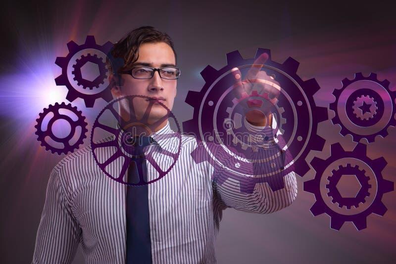 Affärsmannen med kugghjulkugghjulet i teamworkbegrepp royaltyfria foton