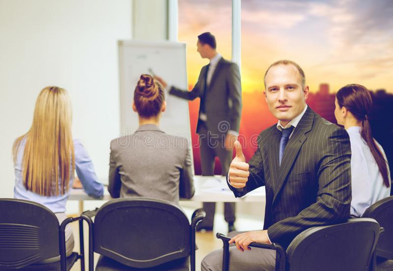 Affärsmannen med lagvisning tummar upp på kontoret arkivfoto