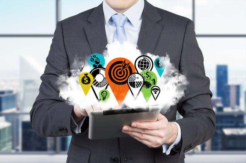 Affärsmannen med minnestavlan och molnet med affärssymbolen sjunker som ett begrepp av den internationella konsulterande affären arkivbild