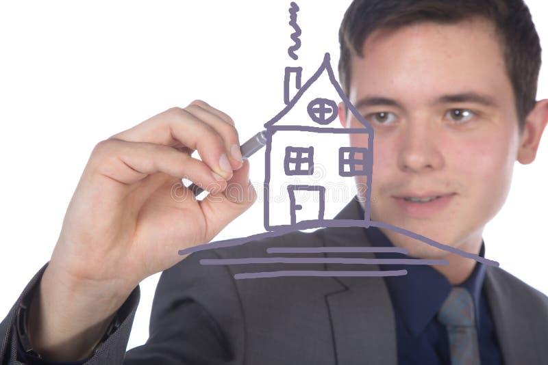 Affärsmannen med pennan målar ett hus royaltyfria foton