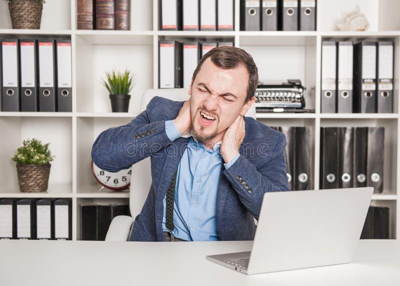 Affärsmannen med smärtar i halsen som i regeringsställning arbetar royaltyfria bilder
