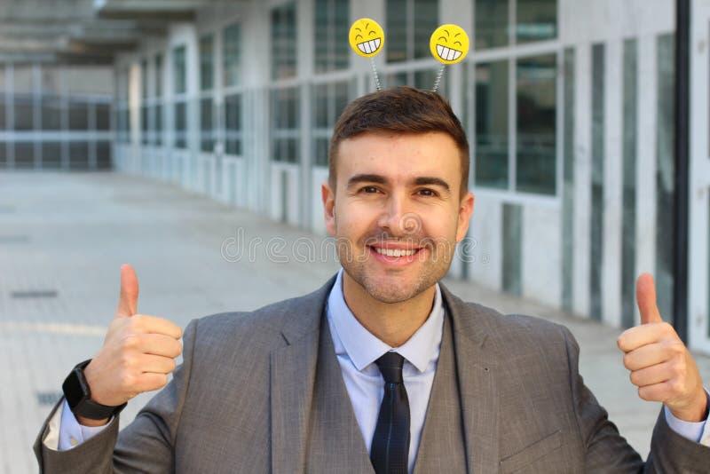 Affärsmannen med smiley vänder mot upp att ge sig för antenner tummar royaltyfria foton