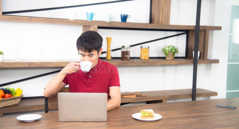 Affärsmannen med tillfällig röd t-skjorta messaging på mobiltelefonen som dricker kaffe och äter smörgåsen, ung man som arbetar p arkivfoto