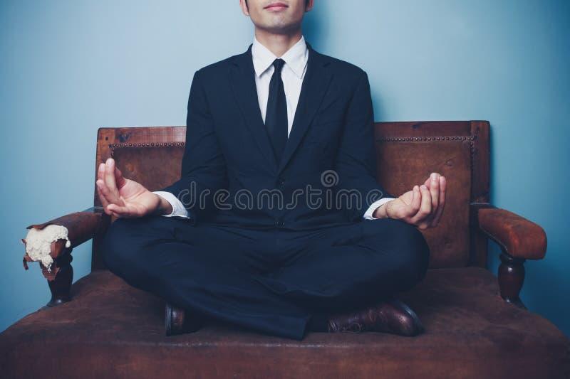 Affärsmannen mediterar på soffan arkivfoto