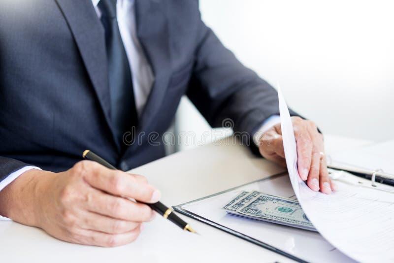 Affärsmannen mottar pengar i kuvertet erbjöd i mappen som tar mutan och undertecknar ett avtal - anti-bestickning och korruption royaltyfria bilder