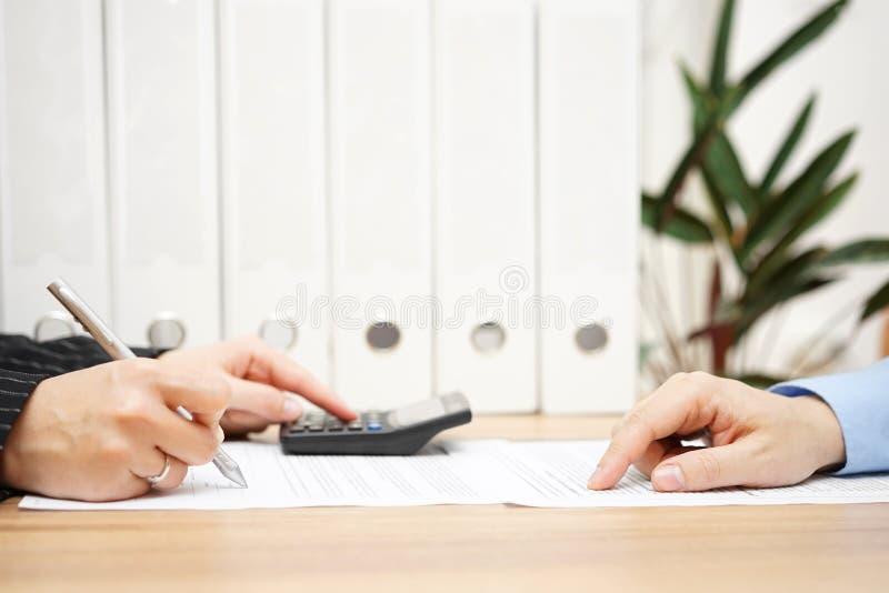 Affärsmannen och affärskvinnan analyserar på finansiella nummer royaltyfria bilder