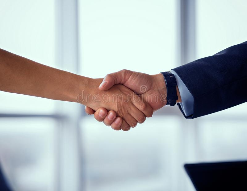Affärsmannen och affärskvinnan skakar händer på överenskommelse royaltyfria foton
