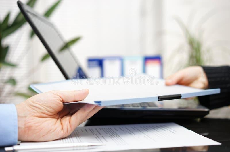 Affärsmannen och affärskvinnan utbyter dokumentet eller contrac royaltyfri bild