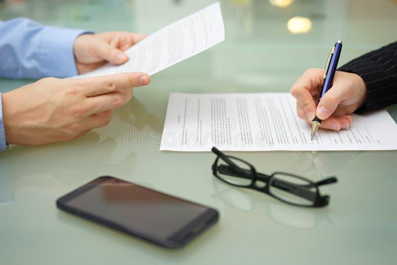 Affärsmannen och kvinnan är läsa och underteckna avtalet arkivfoton